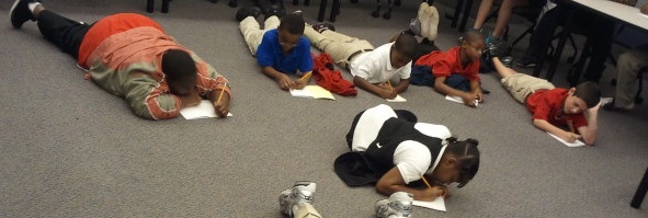 Several children lie on the floor to write as part of NDOW 2011